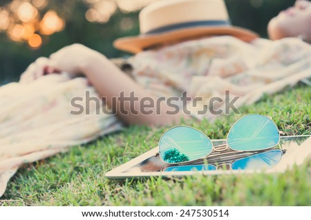 fahsion sun glasses with young woman sleeping in background, vintage style - stock photo