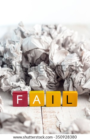 Fail concept colorful block word with trash balls paper behind - stock photo
