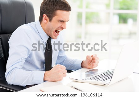 Failed again. Furious young man in shirt and tie looking at computer monitor and shouting while sitting at his working place - stock photo