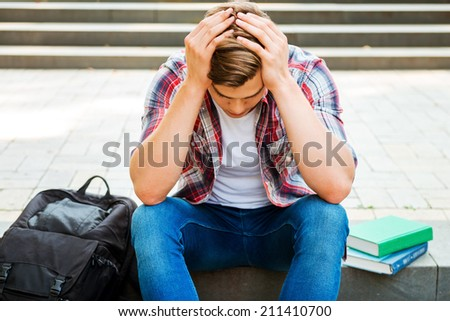 Failed again. Top view of frustrated male student touching his head with hands and looking down while sitting at the outdoors staircase with books and backpack laying near him - stock photo