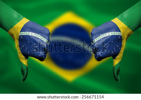 failure of Brazil - hands gesturing thumbs down in front of flag - stock photo