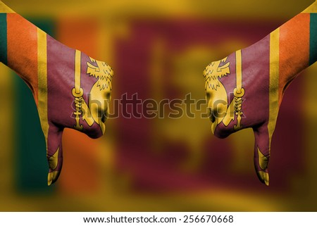failure of Sri Lanka - hands gesturing thumbs down in front of flag - stock photo