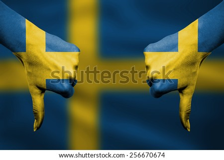 failure of Sweden - hands gesturing thumbs down in front of flag - stock photo