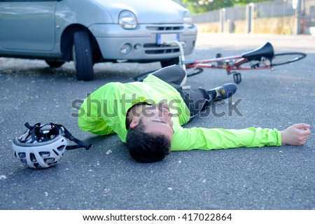 fainted aching man after bicycle accident on the asphalt - stock photo