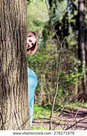 Fair hair pregnant woman peeping out of the tree so you can see not only her face but also her belly - stock photo