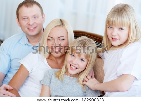 Fair-haired family of four smiling for the camera