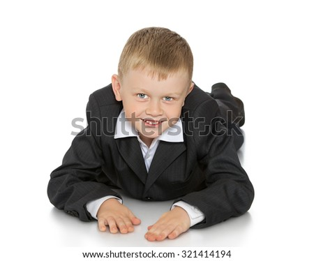 Fair-haired little boy lying on the floor and looks into the camera. The boy is dressed in a gray suit-Isolated on white background