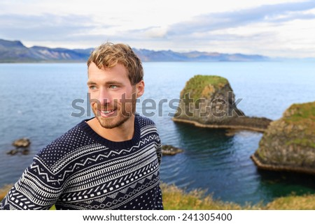 Fair isle sweater. Handsome man portrait in beautiful nature landscape. Young caucasian male model in his 20s smiling in by the ocean sea in Arnarstapi, Snaefellsnes, Iceland. - stock photo