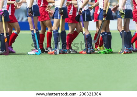 Fair Play concept for sportsmanship, showing two oppsing teams of women field hockey players shaking hands after the line-up of an important match. - stock photo