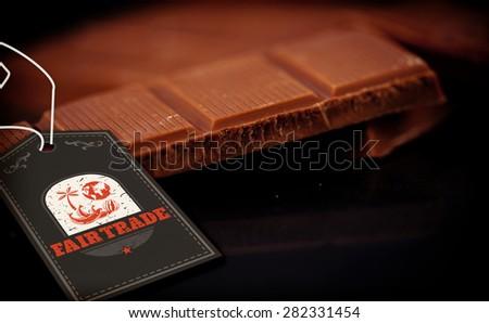 Fair Trade graphic against chocolate bar lying on chocolate - stock photo