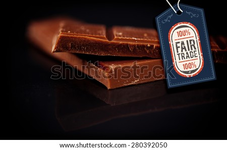 Fair Trade graphic against two blurred bar of dark chocolate - stock photo