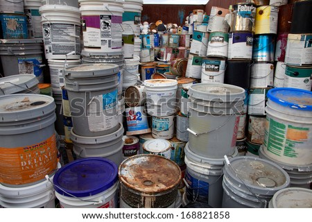 FAIRFAX, VA - DECEMBER 5: A collection of different sizes paint cans, glue buckets, mastic and toxic and hazardous material stacked at a recycling facility on December 5, 2013 in Fairfax, VA. - stock photo