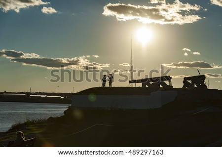 Fairhaven, Massachusetts, USA - September 24, 2016: Reenactors  silhouetted by sun while preparing for firing of cannon at Fort Phoenix in Fairhaven, Massachusetts in a Revolutionary War reenactment