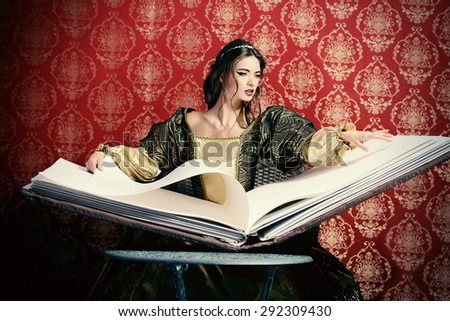 Fairy beautiful witch reads magic book of spells. Vintage style. Renaissance. Barocco. Halloween. - stock photo