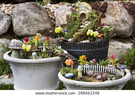 Fairy garden in a flower pot with walking path, wooden bridges and a fairy house.  - stock photo