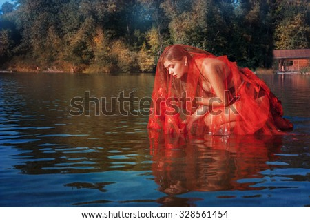 Fairy girl sitting on the water. In her red cape like a veil. - stock photo