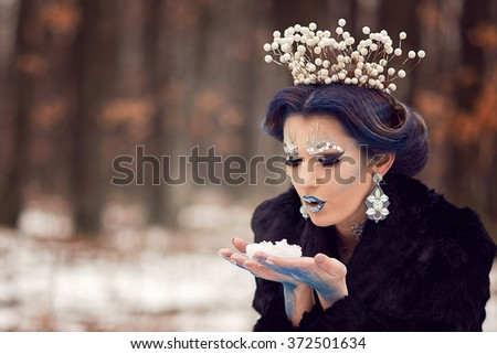 Fairy Snow Queen in elegant blue dress standing in a magic winter forest. Beauty, fashion.  - stock photo