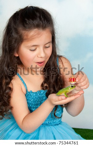 Fairy tale girl putting a golden crown on a frog prince - stock photo