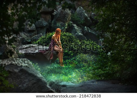 Fairy tale. Princess in a mystical garden pensively looking down - stock photo