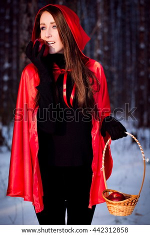 "fairy tale "" Red Riding Hood "" in the forest. girl in red coat goes through the woods. woman holding basket with red apples - stock photo"