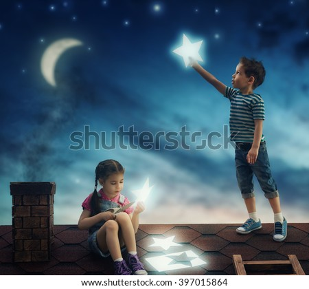 Fairy tale! The children hung the stars in the sky. Boy and girl on the roof cut out stars. - stock photo