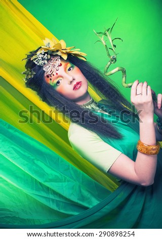 Fairy. Young woman in artistic image with flowers in her hair and with bamboo. - stock photo