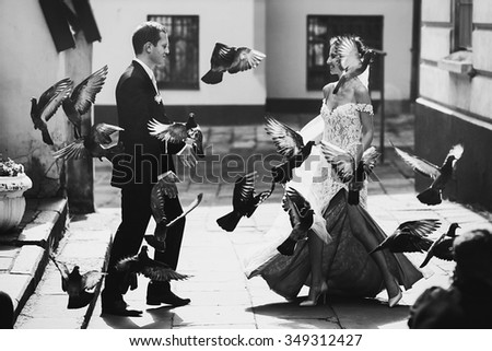 Fairytale beautiful sexual bride walking to handsome groom birds flying b&w