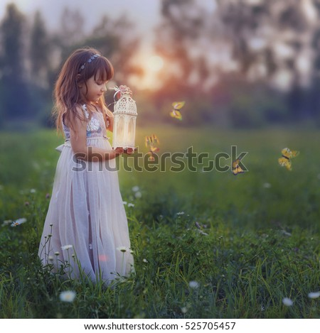 Fairytale portrait of Little girl with butterflies at the sunset