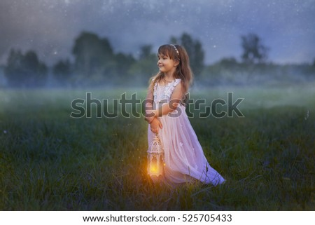 Fairytale portrait of Little girl with lightning at the night field