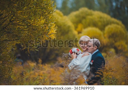 Fairytale romantic valentyne newlywed couple kissing and posing under garden of an old castle bridge at sunset in autumn closeup
