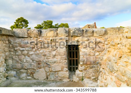 FAISTOS, GREECE - OCTOBER 27, 2014: A grille in a masonry wall in the archaeological site of Phaistos in Crete. - stock photo