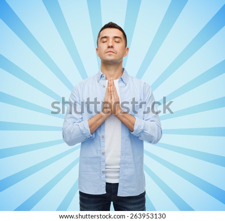 faith in god, religion and people concept - happy man with closed eyes praying over blue burst rays background - stock photo