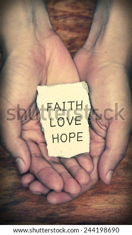 Faith Love Hope stone block in hands with dark background. - stock photo