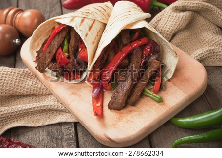 Fajitas, mexican beef stripes with grilled vegetable in tortilla wraps - stock photo
