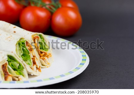 Fajitas on paper plate with tomatoes on background. - stock photo