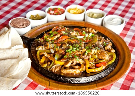 Fajitas with marinated meat, onion, sweet pepper and sauce  - stock photo