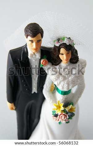 fake bride and groom figures on a white wedding cake - stock photo