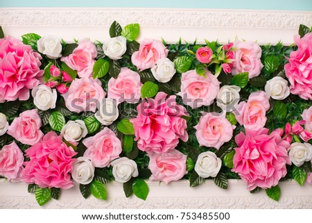 fake flowers composition in white frame blue background