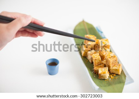 Fake fried tofu (using eggplant replace to tofu) on Japanese bamboo leaf with small cup of plum sauce