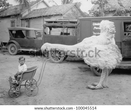Fake ostrich pushing boy in stroller - stock photo