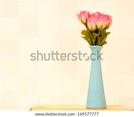 fake pink rose on blue jar.