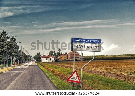 fake road sign of a quiet countryside village inviting to have a rest away from stress