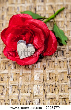 fake satin red rose with a wooden heart inside - stock photo