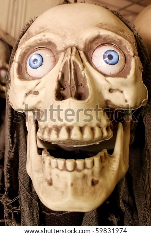 Fake skull with blue eyes - stock photo