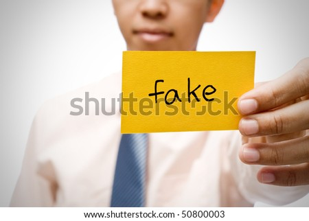 Fake word on  yellow card holding by businessman. - stock photo