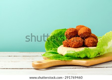 Falafel balls served with pita on a wooden board - stock photo