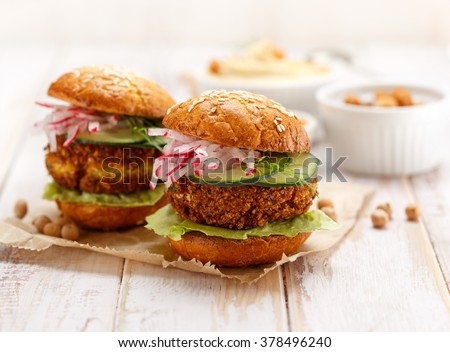 Falafel burger with addition of fresh cucumber, radish and Iceberg lettuce on a wooden rustic table. Healthy and delicious  vegetarian dish - stock photo