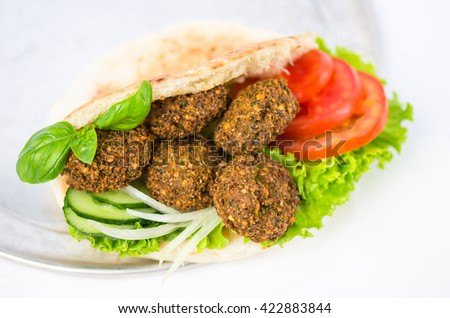 Falafel in pita bread and vegetables - Oriental cuisine. Tasty street food . Excellent choice for lunch and dinner. Close-up on a white background .