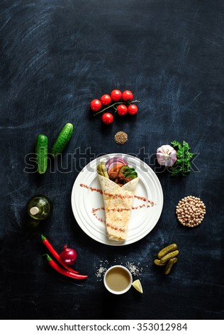 Falafel on a white plate with ingredients laid out on a spiral on a blackboard. View from above - stock photo