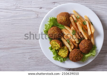 falafel with French fries, lettuce on a white plate top view horizontal   - stock photo